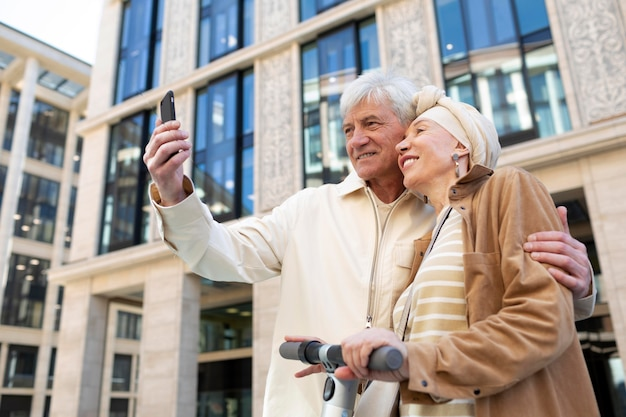 Couple de personnes âgées chevauchant un scooter électrique dans la ville et prenant un selfie