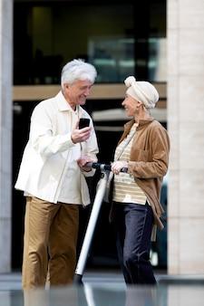 Couple de personnes âgées chevauchant un scooter électrique dans la ville et utilisant un smartphone