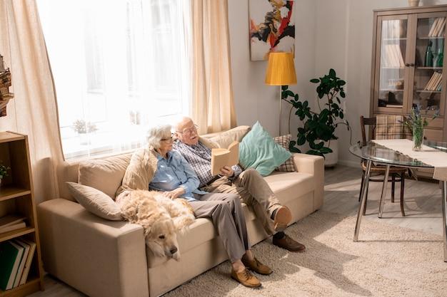Couple de personnes âgées avec chien sur canapé