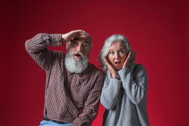 Couple de personnes âgées choqué à la recherche d'appareil photo sur fond rouge