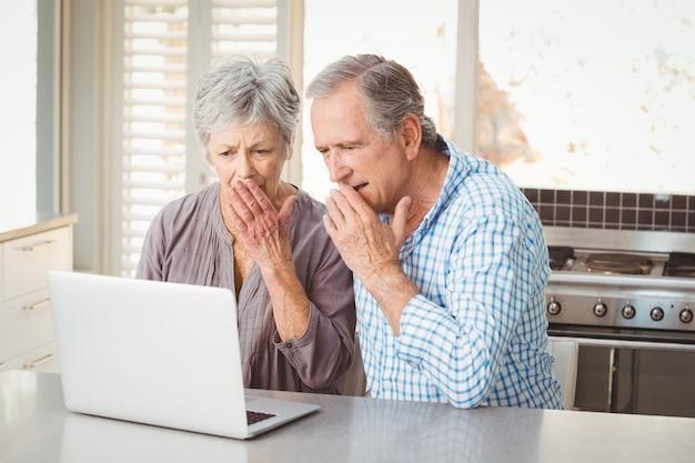 Couple de personnes âgées choqué à la recherche d'un ordinateur portable