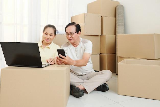 Couple de personnes âgées commande des déménageurs