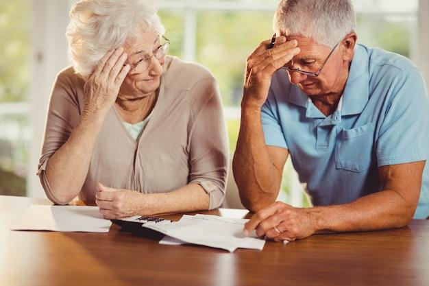 Couple de personnes âgées comptant des factures à la maison