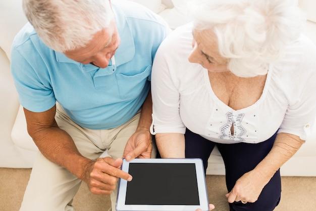 Couple de personnes âgées concentré à l'aide d'une tablette à la maison