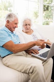 Couple de personnes âgées concentré à la maison avec un ordinateur portable