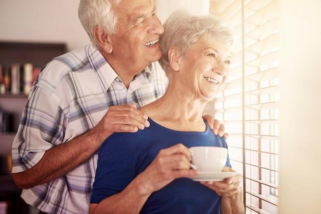 Couple de personnes âgées à côté de la fenêtre