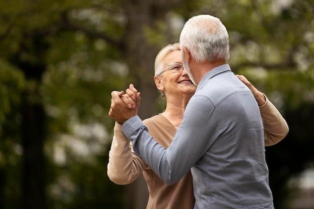 Couple de personnes âgées coup moyen dansant dans la nature