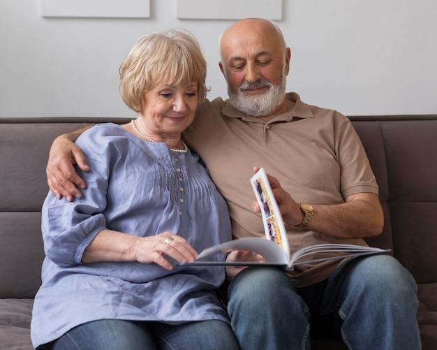 Couple de personnes âgées coup moyen lisant ensemble