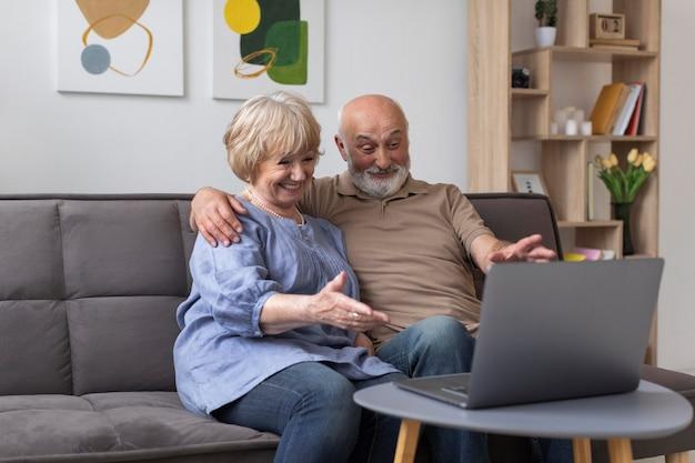 Couple de personnes âgées à coup moyen à la recherche d'un ordinateur portable