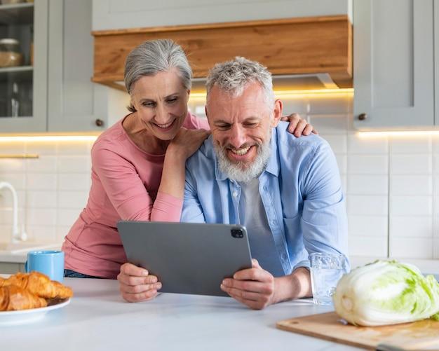 Couple de personnes âgées avec un coup moyen de tablette