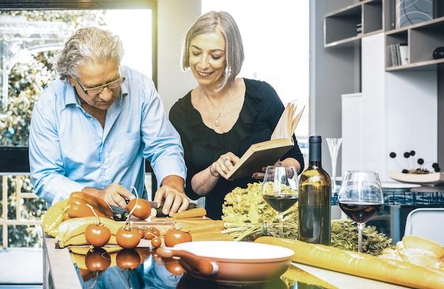Couple de personnes âgées cuisinant des aliments sains et buvant du vin rouge dans la cuisine de la maison