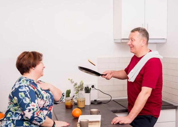 Couple de personnes âgées cuisinant des crêpes