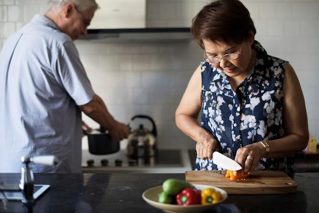 Couple de personnes âgées cuisiner ensemble