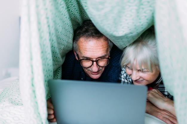 Couple de personnes âgées dans la grotte dans le lit avec un ordinateur portable