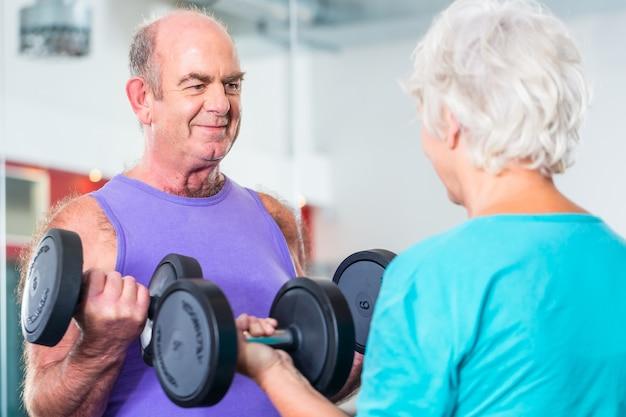 Couple de personnes âgées dans l'haltère de gym