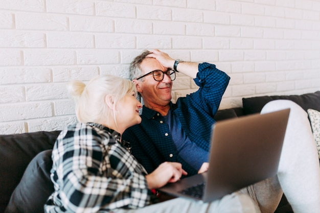 Couple de personnes âgées dans la maison de retraite avec ordinateur portable