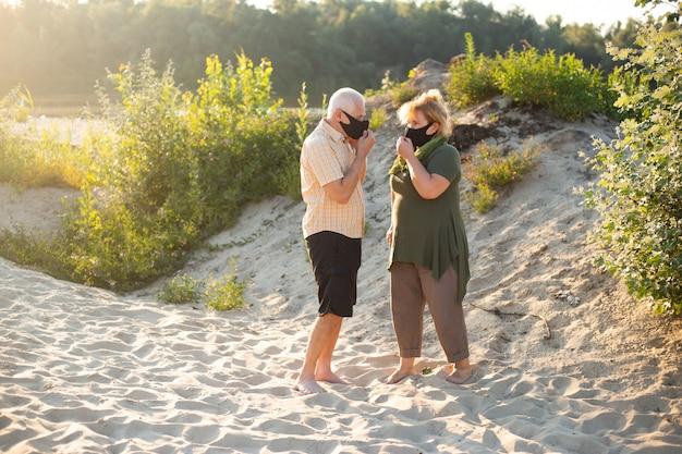 Couple de personnes âgées dans des masques médicaux pour se protéger du coronavirus à l'extérieur dans la nature estivale