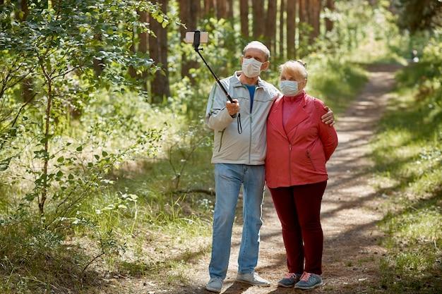 Un couple de personnes âgées dans des masques de protection prend un selfie sur un smartphone et se promène dans le parc