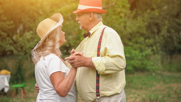 Couple de personnes âgées dansant dans le jardin