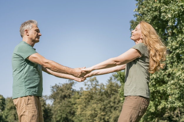 Couple de personnes âgées dansant dans le parc