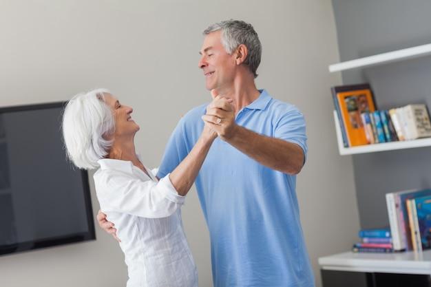 Couple de personnes âgées dansant dans le salon