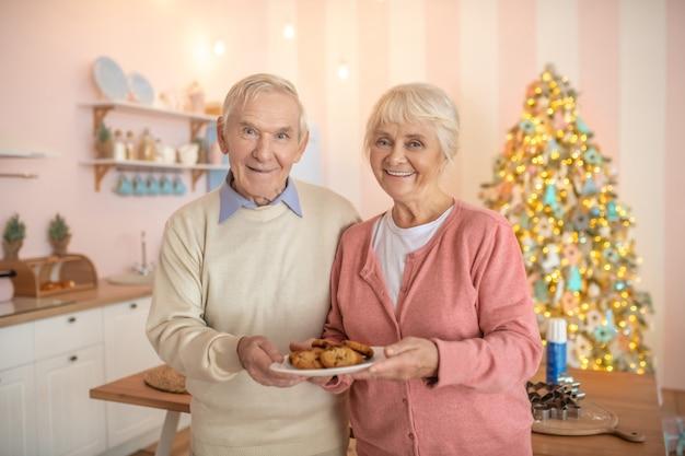 Couple de personnes âgées debout dans la cuisine avec une assiette avec des pâtisseries