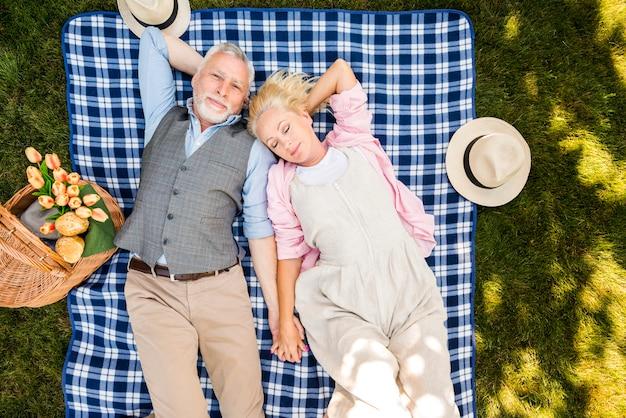 Couple de personnes âgées détendu, couché sur l'herbe