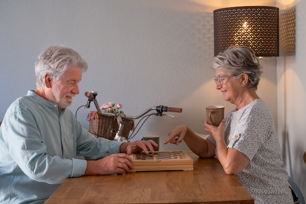 Un couple de personnes âgées détendu passe du temps ensemble à la maison en jouant à un jeu de dames sur une table en bois.