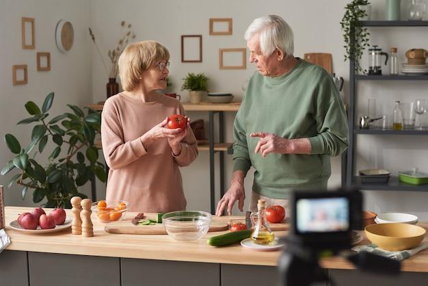 Couple de personnes âgées discutant des ingrédients alimentaires et tirant un blog sur la nourriture en se tenant debout dans la cuisine