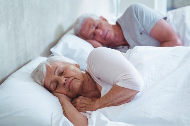 Couple de personnes âgées dormir sur le lit
