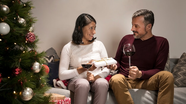 Couple de personnes âgées échangeant des cadeaux de noël