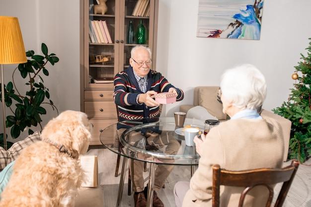 Couple de personnes âgées échangeant des cadeaux