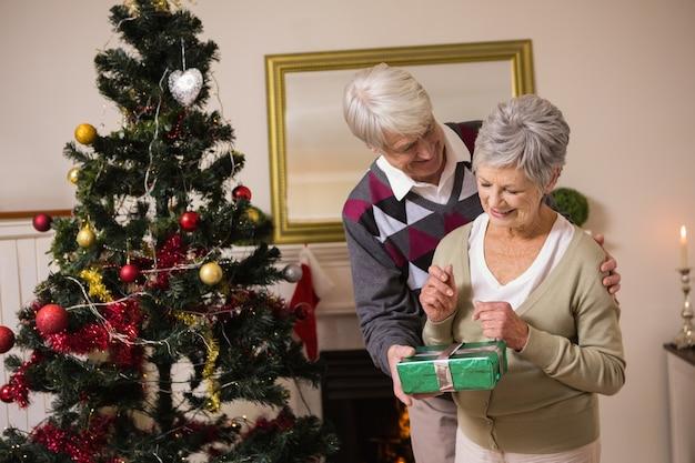Couple de personnes âgées échanger des cadeaux par leur arbre de noël
