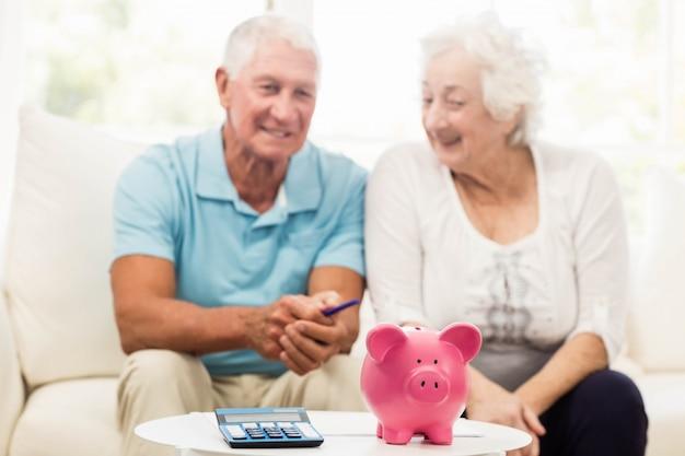 Couple de personnes âgées économiser de l'argent à la maison