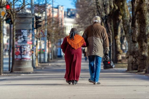 Un couple de personnes âgées entre les mains se promène dans la rue.