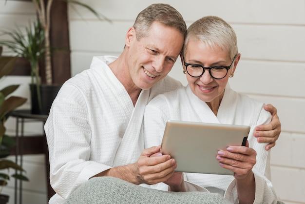 Couple de personnes âgées étant proche tout en regardant sur une tablette