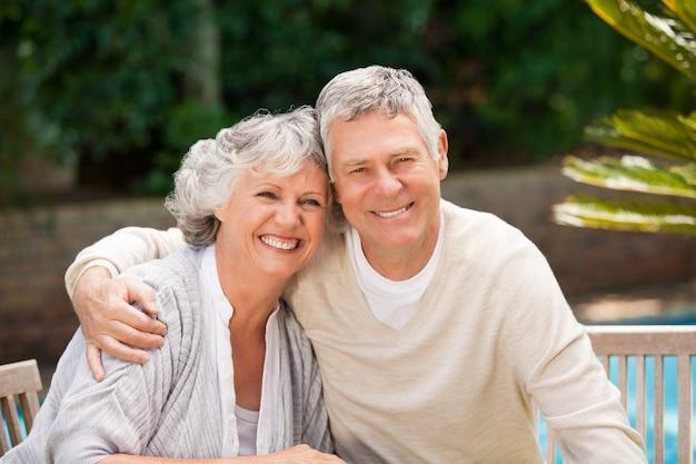 Couple de personnes âgées étreindre dans le jardin