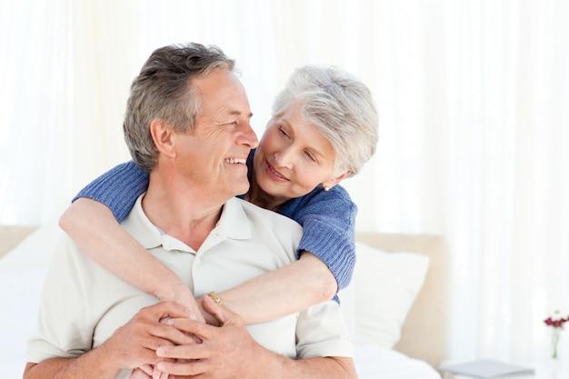Couple de personnes âgées étreindre sur leur lit