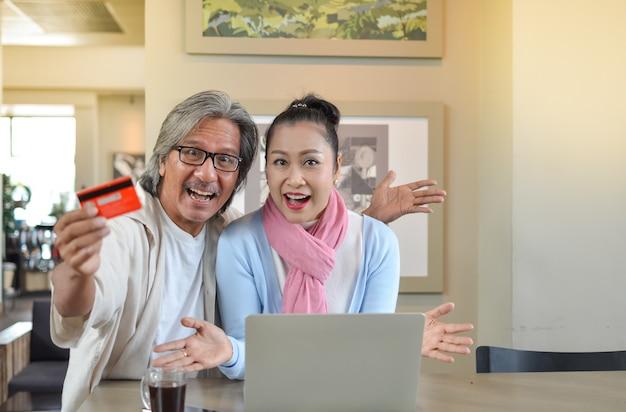 Couple de personnes âgées étudiant l'utilisation d'un ordinateur portable.
