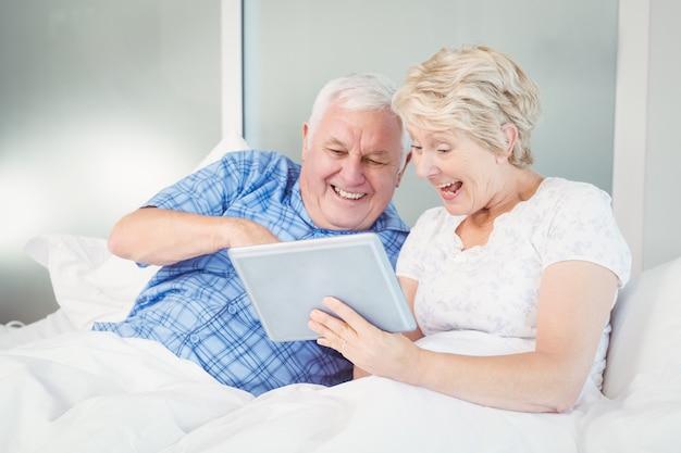 Couple de personnes âgées excité à l'aide d'une tablette numérique sur le lit
