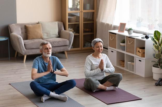 Couple de personnes âgées exerçant ensemble à la maison