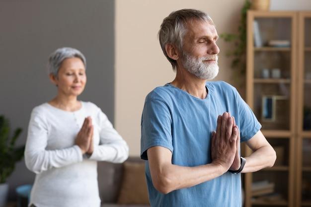 Couple de personnes âgées exerçant à la maison