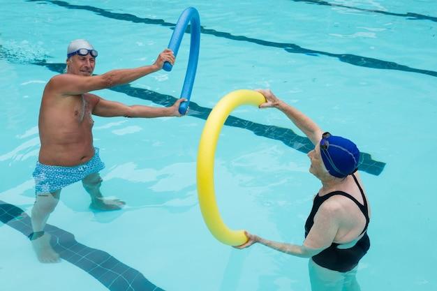 Couple de personnes âgées exerçant avec des nouilles de piscine dans la piscine