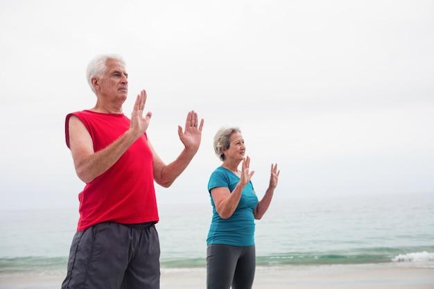 Couple de personnes âgées exerçant sur la plage