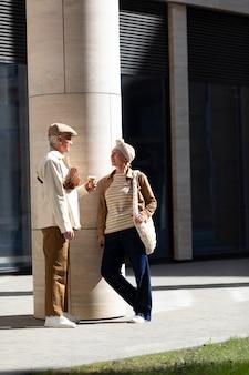 Couple de personnes âgées à l'extérieur de la ville avec une tasse de café