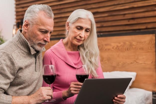 Couple de personnes âgées faible angle boire du vin