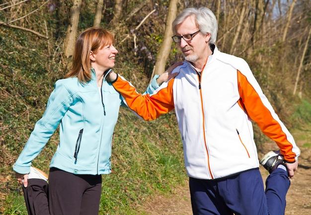 Couple de personnes âgées faisant de l'exercice dans le parc