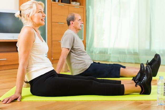 Couple de personnes âgées faisant des exercices d'intérieur