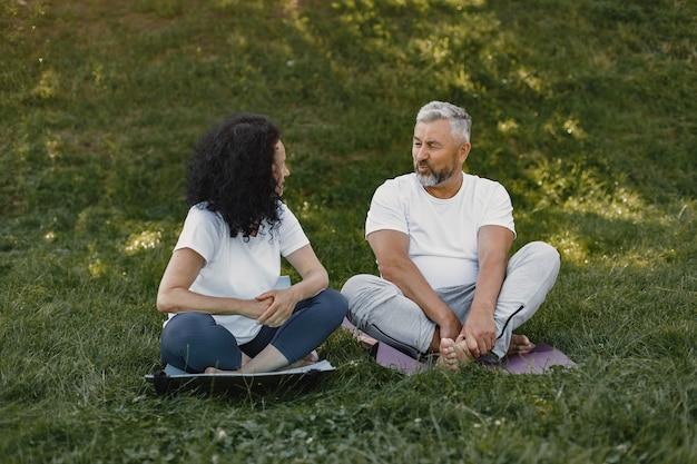 Couple de personnes âgées fait du yoga à l'extérieur. s'étendant dans le parc pendant le lever du soleil. brunette dans un t-shirt blanc.