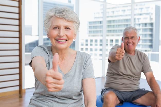 Couple de personnes âgées gesticulant pouce en l'air au gymnase médical